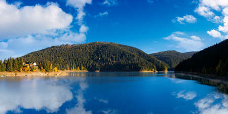 panorama of mountain lake in autumn season. beautiful countryside scenery on a sunny morning. bright blue sky with fluffy clouds reflecting on the water surface Stock Photo