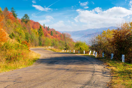 old serpentine road in mountains. beautiful autumn scenery on a sunny day. trees in colorful foliage. countryside journey on a weekend concept