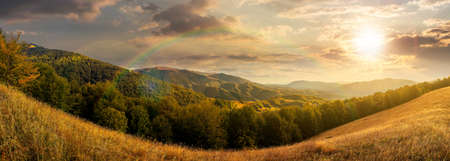 mountainous countryside at sunset. beautiful panorama of carpathians. valley of borzhava ridge in the distance in evening light. clouds on the sky. sunny weather Stock Photo