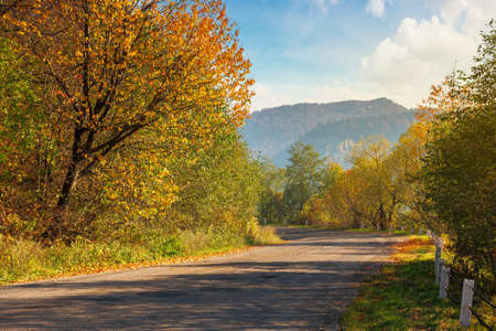 old asphalt road in mountains. beautiful autumn scenery on a sunny day. trees in colorful foliage. countryside journey on a weekend concept