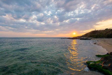 sunrise at the black sea. wonderful calm landscape with rocks on the beach beneath a cloudy sky. velvet season vacations. travel bulgaria concept