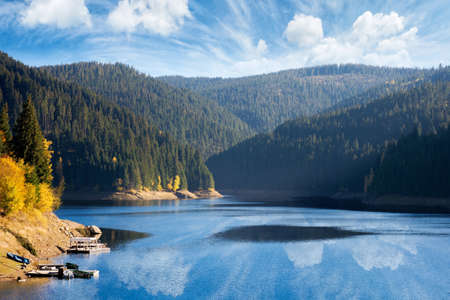 mountain lake in autumn season. beautiful countryside scenery on a sunny morning. bright blue sky with fluffy clouds reflecting on the water surface Stock Photo