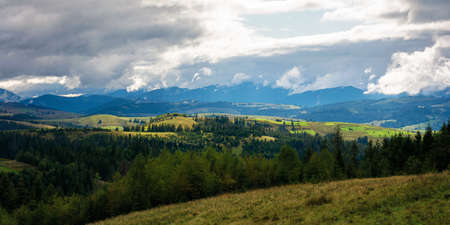 beautiful scenery of mountainous countryside. clouds above the hills rolling in to the distant valley. carpathian landscape in dappled light. dramatic weather conditions.