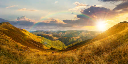 mountain landscape in autumn at sunset. dry colorful grass on the hills. ridge behind the distant valley in evening light. view from the top of a hill. clouds on the sky