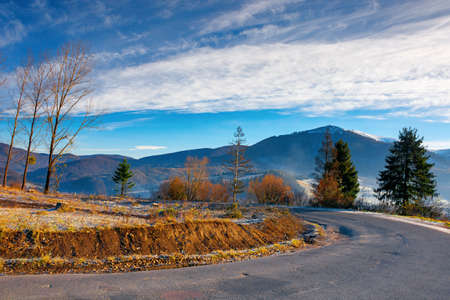 mountain road winding through countryside. beautiful autumn scenery at sunrise. village in the valley and snow capped peaks in the distance