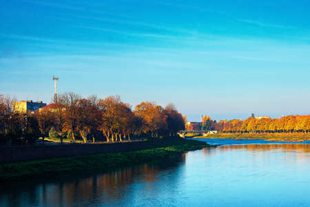 river uzh at sunrise. beautiful cityscape autumn scenery. linden alley in fall color in morning light. location uzhgorod, ukraine 免版税图像