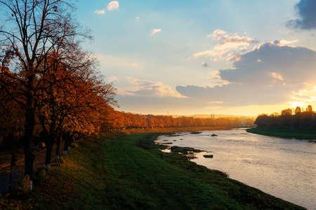 river uzh at sunrise. beautiful cityscape autumn scenery. linden alley in fall color in morning light. location uzhgorod, ukraine Stock Photo