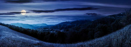 mountainous countryside at night. beautiful panorama of carpathians. valley of borzhava ridge in the distance in full moon light. clouds on the sky