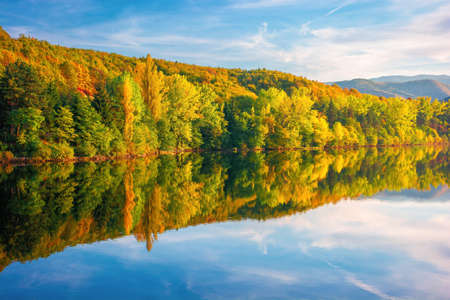 gilau lake of cluj country in evening light. beautiful landscape of romania in autumn. reflection on the calm water surface. trees in colorful foliage. sunny weather Stock Photo