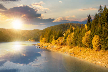 mountain lake in autumn season at sunset. beautiful countryside scenery in evening light. blue sky with fluffy clouds reflecting on the water surface