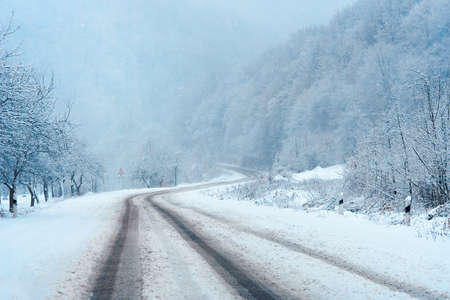 country road through mountains in winter. beautiful nature scenery. snow weather Stock Photo