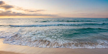 sunrise at the sea. beautiful summer landscape on the sandy beach. green waves rush on the shore in golden light Stock Photo