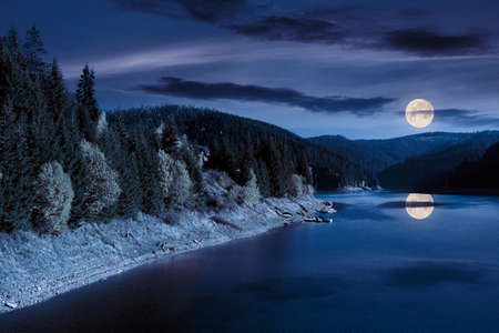 mountain lake in autumn season at night. beautiful countryside scenery in full moon light. blue sky with fluffy clouds reflecting on the water surface