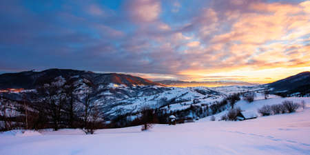 winter mountain landscape at sunrise. trees and fields on snow covered hills. ridge in the distance beneath a dramatic sky with clouds. beautiful carpathian countryside