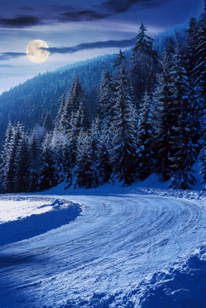 snow covered road through forest in mountains at night. beautiful winter scenery in full moon light. spruce trees along the path in hoarfrost and sunlight