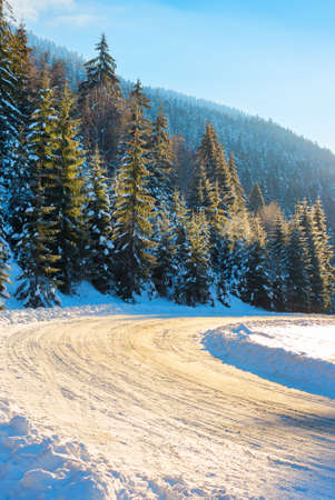 snow covered road through forest in mountains. beautiful winter scenery at sunrise. spruce trees along the path in hoarfrost and sunlight Stock Photo