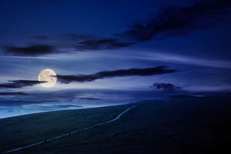 travel carpathian mountains in summer at night. road through green grassy meadows in the distance in full moon light. idyllic landscape with clouds on the blue sky. Stock Photo