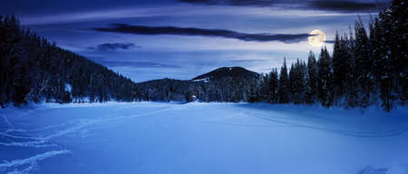 snow covered mountain lake at night. green spruce trees on the shore in full moon light. clouds on the sky Stock Photo