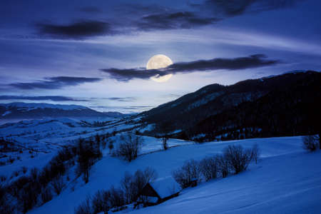 winter landscape in mountains at night. beautiful rural area of carpathian mountains with snow covered hills. glowing clouds on the sky in full moon light. frosty weather
