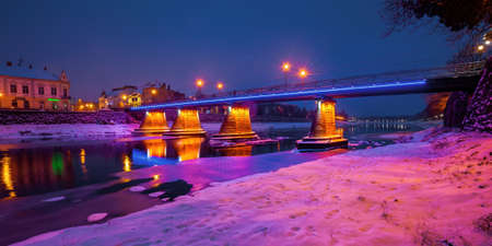 uzhhorod, ukraine - 26 DEC, 2016: old town on a christmas night. beautiful cityscape by the river. snow on the embankment. bridge and lanterns glowing in the distance
