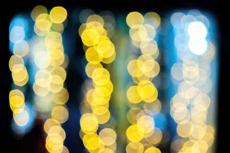 yellow blurry Christmas lights on the streets. holiday night background with bokeh effect.