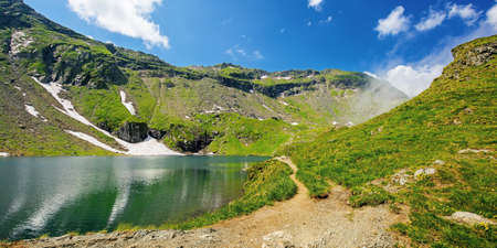 balea lake in fagaras mountain of romania. beautiful landscape in summertime. rocky slopes with grass in snow. sunny weather with fluffy clouds on the sky. popular travel destination Stock Photo