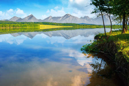 composite landscape of mountain lake in summer. beautiful nature scenery on a sunny morning. sky and ridge reflecting in the calm water surface. trees on the shore