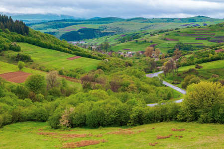 carpathian countryside in spring. beautiful rural landscape in mountain. wet grassy meadow on fresh morning. road winding through valley to village. distant ridge in the clouds