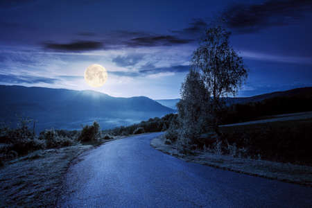 countryside road in mountains at night. beautiful view in to the distant foggy valley from the top of the pass. trees along the way in full moon light. wonderful rural landscape in summer Stock Photo