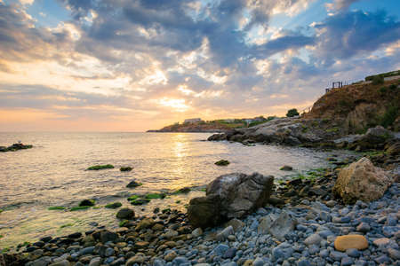 dramatic sunrise at the sea. beautiful seascape with clouds on the sky above horizon. rocks and pebbles on the coast Stock Photo