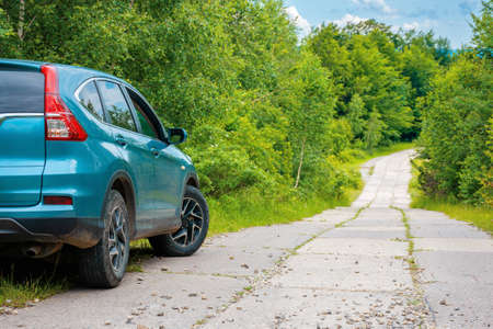 suv on the concrete roadside in the forest. travel countryside concept. beautiful nature scenery in summer Stock Photo