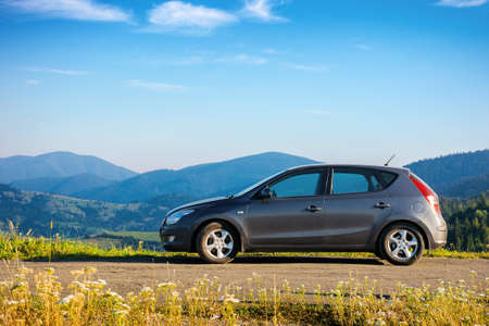 car on the concrete parking on top of the mountain in morning light. travel countryside concept. beautiful nature scenery views in summer with fluffy clouds on the blue sky Stock Photo