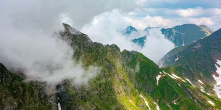 fagaras mountain landscape in summer. wonderful nature scenery with clouds on the peaks and snow in the valley. hills in grass and rocks. discover carpathins of romanian concept