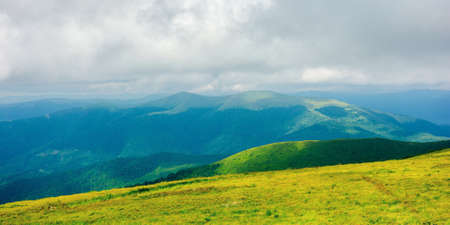 mountain landscape in summer on a cloudy day. grass covered hillside meadow. carpathian watershed ridge in the distance Stock Photo