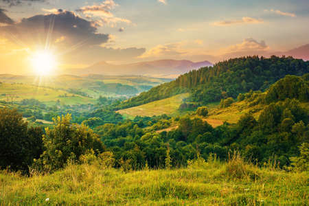 mountainous rural landscape at sunset. beautiful scenery with forests, hills and meadows in evening light. ridge with high peak in the distance. village in the distant valley Stock Photo