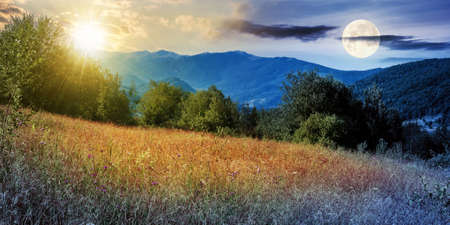 day and night time change concept above rural field in mountains. beautiful summer landscape of carpathian countryside with sun and mooon. trees on the hill, forested ridge in the distance beneath a sky with clouds Stock Photo