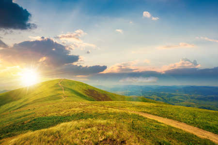 mountain landscape on a bright spring sunset. path through meadow in grass on the hill in evening light. wonderful weather with fluffy clouds on the sky. borzhava ridge of carpathians Stock Photo