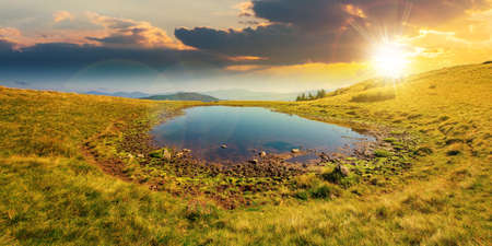 pond on the mountain meadow at sunset. wonderful summer landscape in evening light. grass and trees on the hills. ridge in the distance. beautiful wide panorama Stock Photo