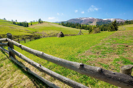 mountainous rural landscape in spring. haystack on a grassy field behind the wooden fence on rolling hills. snow capped ridge in the distance. beautiful countryside scenery on a bright sunny day Stock Photo