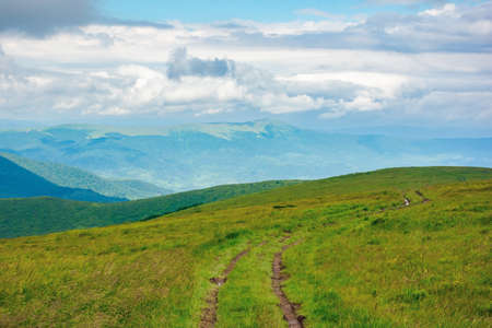 path through mountain meadow. beautiful carpathian landscape in summertime. clouds on the sky above the distant ridge. windy weather