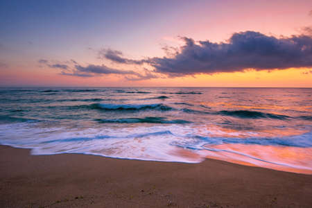 sea beach with dramatic sky at sunrise. beautiful vacation background. waves rolling on the sand in morning light Stock Photo
