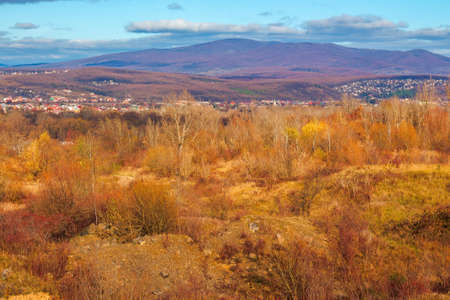 rural valley in the morning. beautiful autumn scenery in mountains. town in the distant valley. clouds on the blue forenoon sky