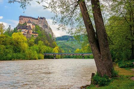 oravsky podzamok, slovakia - MAY 01, 2019: oravsky castle on the hill near the river. popular travel destination. beautiful springtime scenery in dappled light