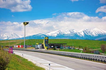 strba, slovakia - 01 MAY 2019: slovnaft gas station on a freeway. sunny scenery with green meadows beneath a blue sky with fluffy clouds. snow capped tatra mountains in the distance. wonderful journey Editorial