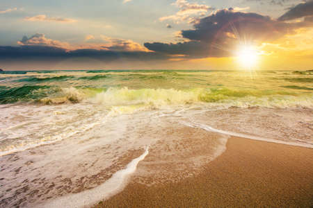 sea tide on a cloudy sunrise. green waves crashing golden sandy beach in morning light. storm weather approaching. summer holiday concept Stock Photo
