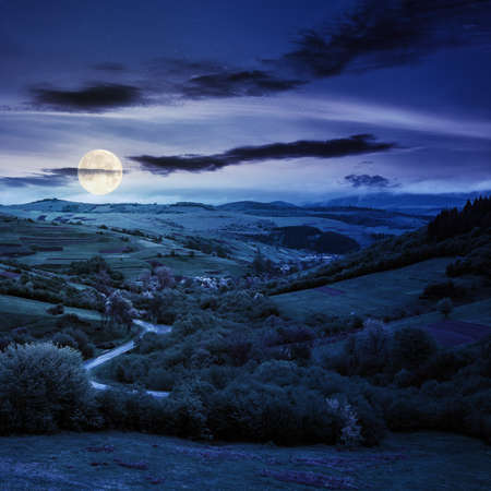 carpathian countryside in spring at night. beautiful rural landscape in mountain. wet grassy meadow in full moon light. road winding through valley to village. distant ridge in the clouds Stock Photo