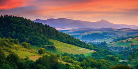 mountainous rural landscape at dawn. beautiful scenery with forests, hills and meadows in morning light. ridge with high peak in the distance. village in the distant valley