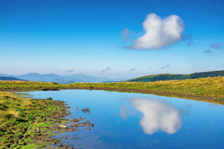 pond on the mountain meadow. beautiful summer landscape in morning light. grass on the hills. ridge in the distance