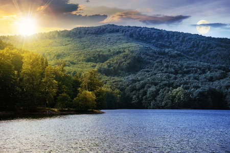 day and night time change concept on a lake among beech forest in summer. beautiful nature landscape in mountains. vihorlat national park with sun and moon on the sky Stock Photo