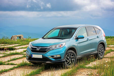 lypovets, ukraine - JUN 22, 2019: suv on the concrete roadside on top of the mountain runa. travel countryside concept. beautiful nature scenery in summer with dramatic sky Editorial